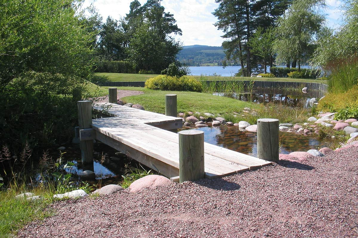 Gartengestaltung mit Steinen: Schöner Kies vor einem See mit Brücke im Garten